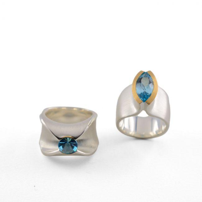 li: Silber 925/- mit GG 750/- Belötung, Blau Topas Navette, re: Silber 925/- mit in GG 750/- gefasstem Blau Topas Sonderschliff